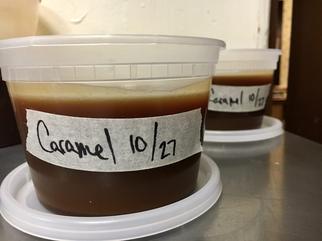 """Two plastic pint containers of caramel sauce with labels that read """"caramel 10/27""""."""