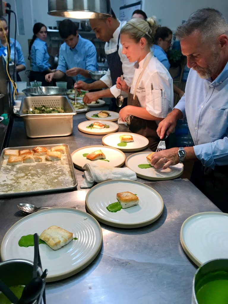 Chefs at the pass plating up fish on a line of plates and servers taking them to the guests.