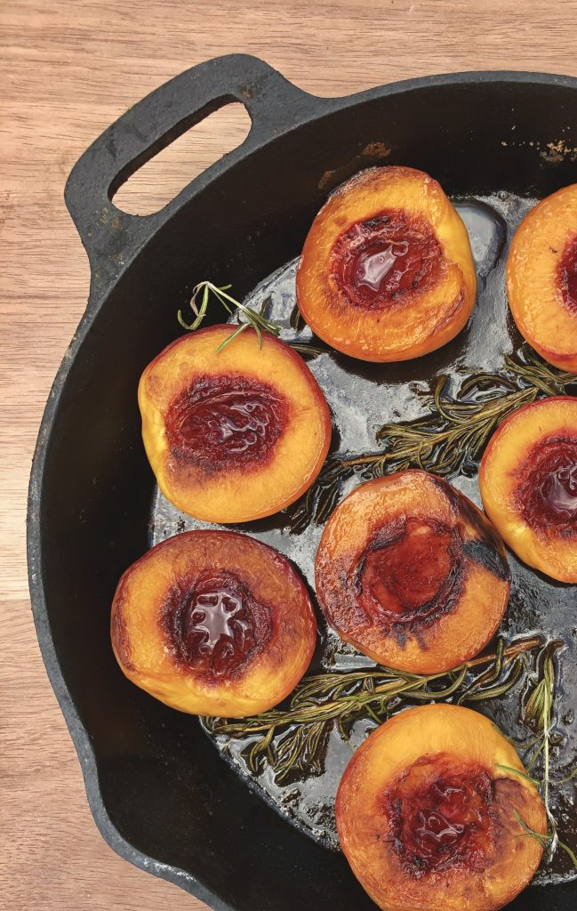Roasted peaches turned cut side up in a cast iron skillet.