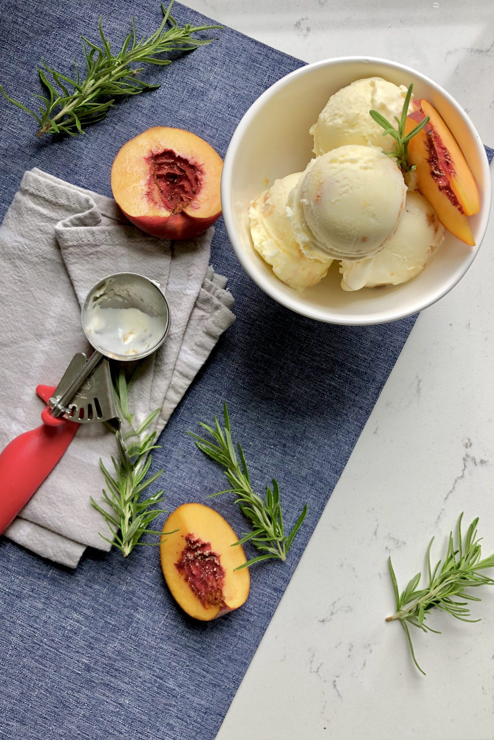 A scene of a few scoops of the roasted peach and rosemary ice cream in a bowl with some peaches and an ice cream scooper.