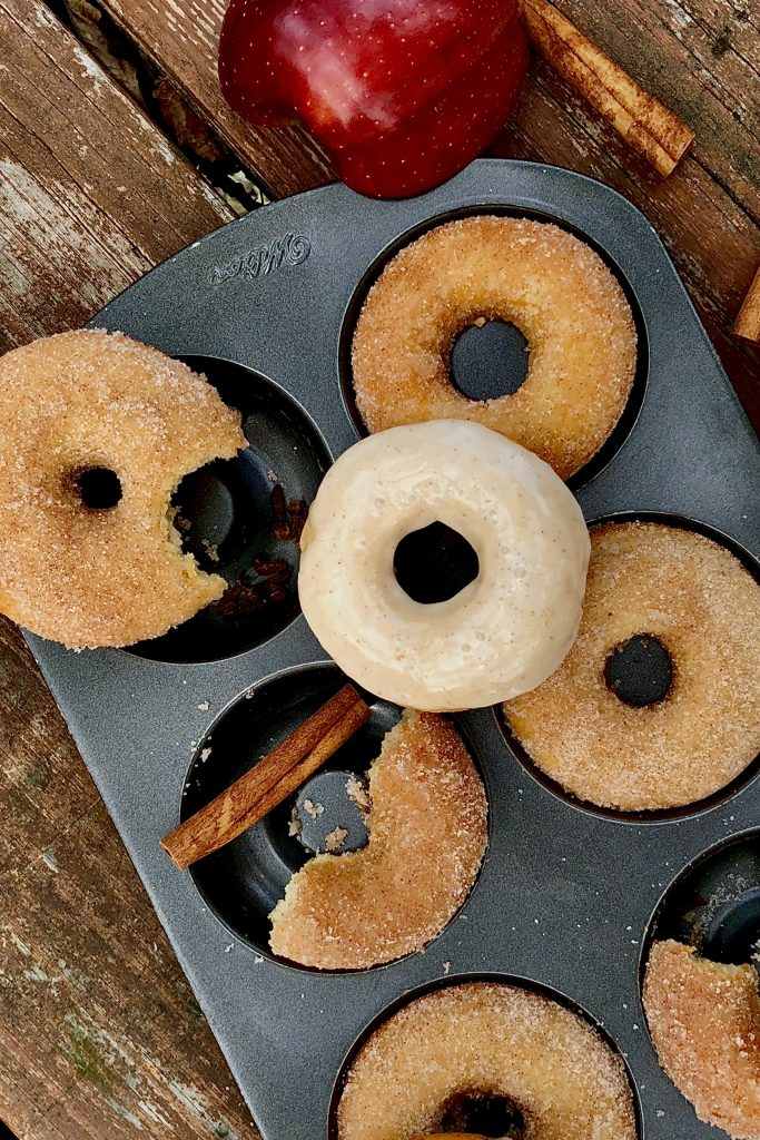baked apple cider donuts tossed in cinnamon sugar in a donut pan