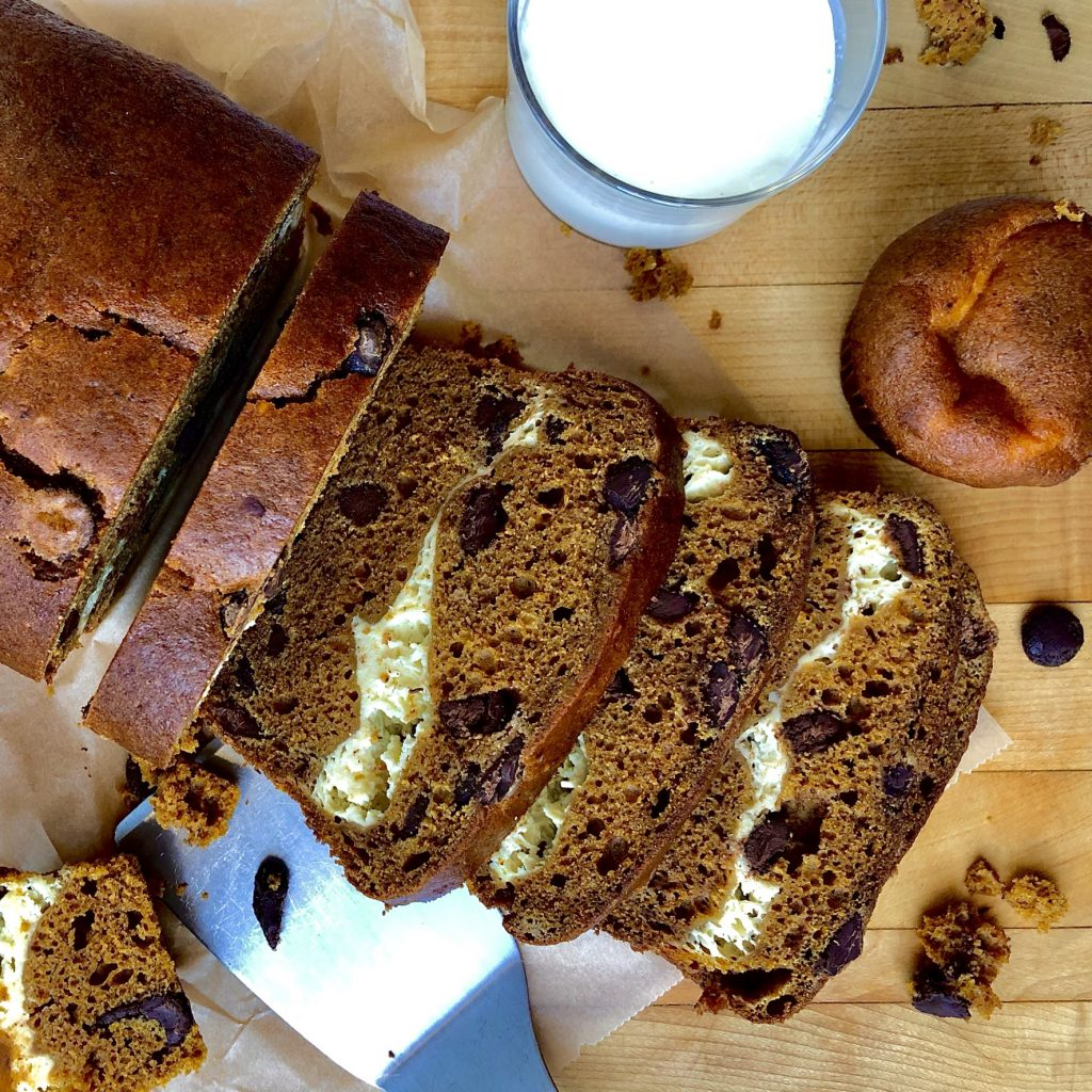 Pumpkin Cheesecake bread sliced on a board with a nice cold glass of milk.