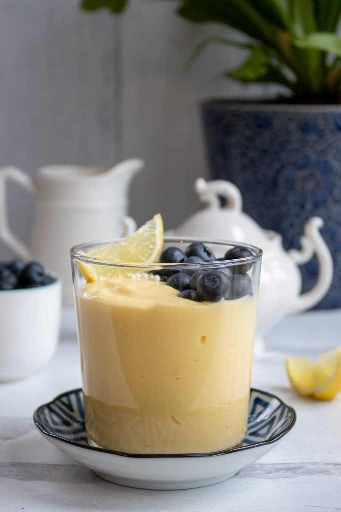 creamy lemon curd in a glass topped with blueberries